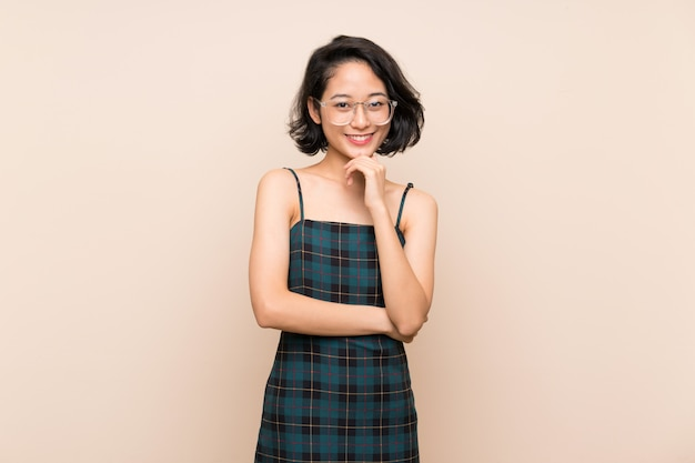 Aziatische jonge vrouw over geïsoleerde gele muur met een bril en glimlachen