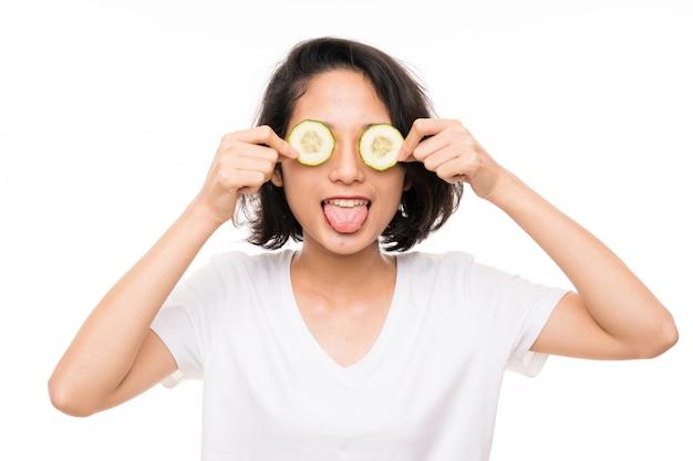 Aziatische jonge vrouw over geïsoleerde holdingsplakken van komkommer