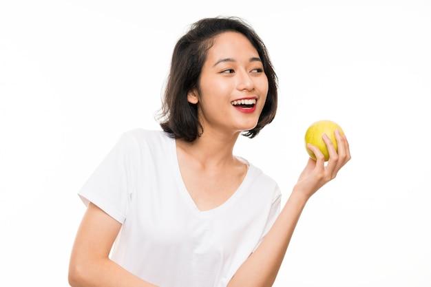 Aziatische jonge vrouw over geïsoleerde muur met een appel