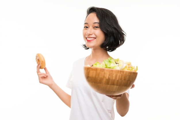 Aziatische jonge vrouw over geïsoleerde muur met salade en doughnut