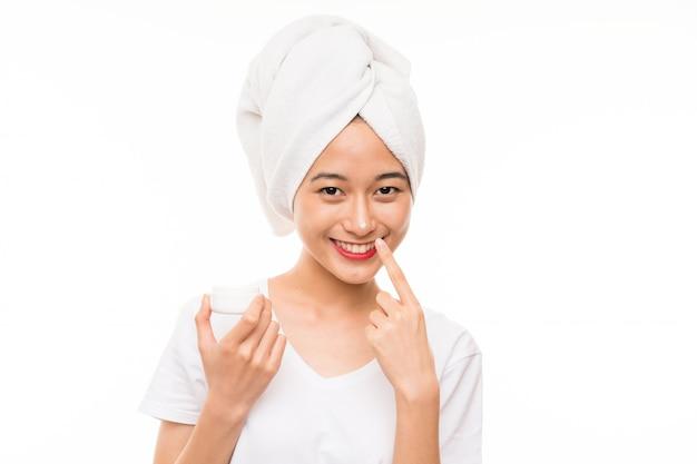 Aziatische jonge vrouw over geïsoleerde muur met vochtinbrengende crème