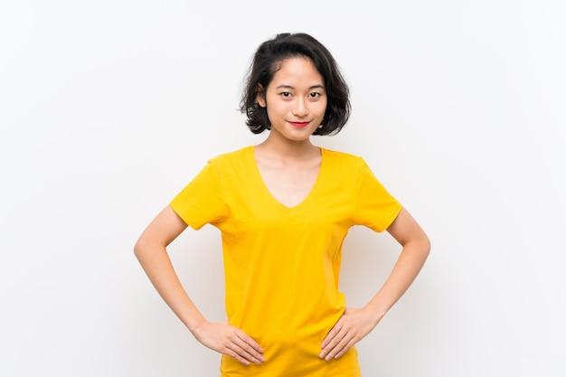 Aziatische jonge vrouw over het geïsoleerde witte stellen met wapens bij heup en het glimlachen