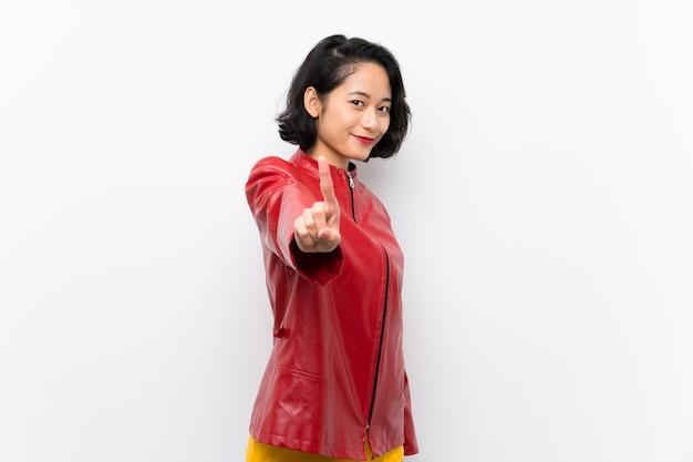 Aziatische jonge vrouw over het tonen van en het opheffen van een vinger