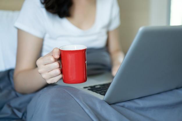 Aziatische jonge vrouw portret in thuis werken concept. gelukkige aziatische vrouw die ok teken toont tijdens het gebruik van videoconferentie met haar vriend tijdens verblijf thuis. blije vrouw die op internet surft.