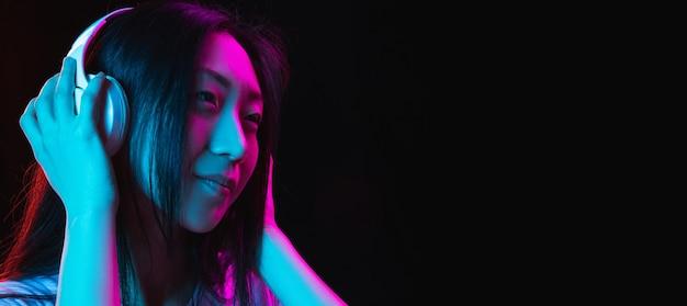 Aziatische jonge vrouw portret op donkere muur in neon concept van menselijke emoties gezichtsuitdrukking jeugd verkoop advertentie