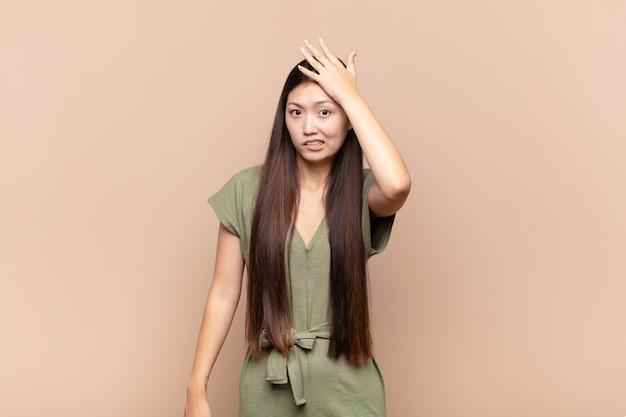 Aziatische jonge vrouw raakt in paniek over een vergeten deadline, voelt zich gestrest, moet een puinhoop of een fout bedekken