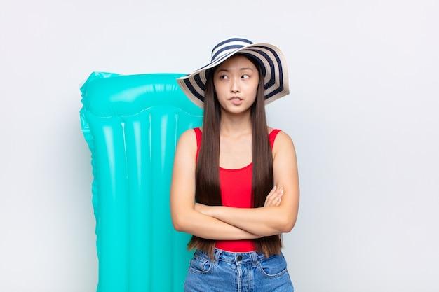 Aziatische jonge vrouw twijfelen of denken, lip bijten en zich onzeker en nerveus voelen