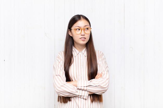 Aziatische jonge vrouw twijfelt of denkt, bijt op lip en voelt zich onzeker en nerveus, op zoek naar ruimte aan de zijkant