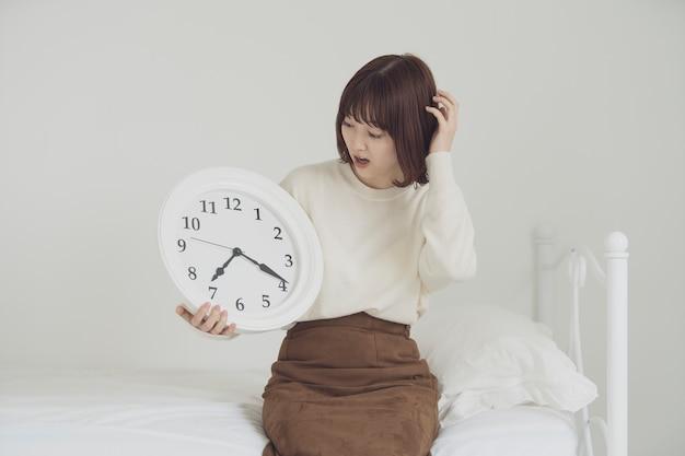 Aziatische jonge vrouw verbaasd om de klok te controleren en laat op tijd te zijn