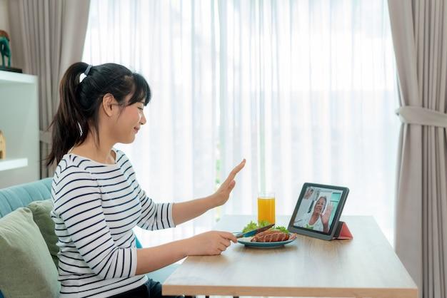 Aziatische jonge vrouw virtueel happy hour ontmoeten en eten samen met haar moeder online
