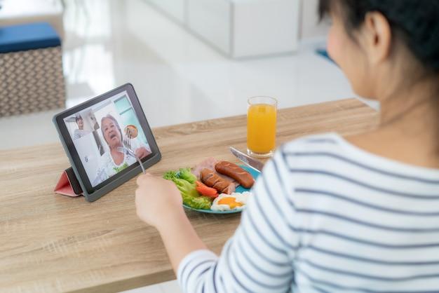 Aziatische jonge vrouw virtuele happy hour vergadering en het eten van voedsel online samen met haar moeder in videoconferentie met digitale tablet voor een online vergadering in videogesprek