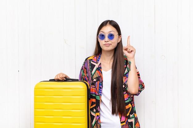 Aziatische jonge vrouw voelt zich als een genie die trots de vinger in de lucht houdt nadat ze een geweldig idee heeft gerealiseerd door eureka te zeggen. vakantie concept