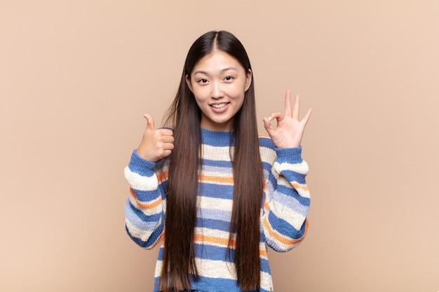Aziatische jonge vrouw voelt zich blij, verbaasd, tevreden en verrast, toont oké en duimen omhoog gebaren, glimlachend