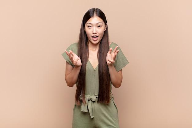 Aziatische jonge vrouw voelt zich extreem geschokt en verrast, angstig en in paniek, met een gestreste en geschokte blik