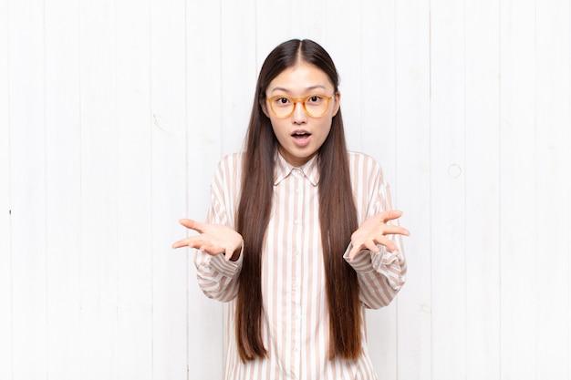 Aziatische jonge vrouw voelt zich extreem geschokt en verrast geïsoleerd