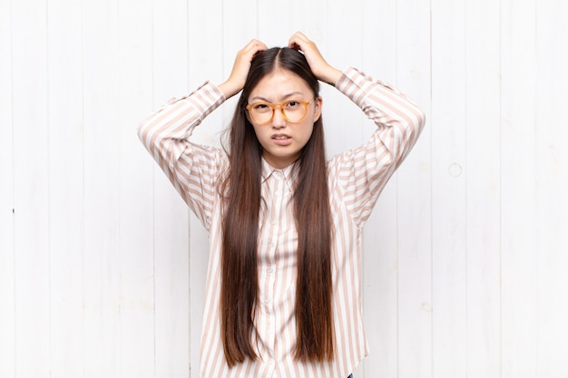 Aziatische jonge vrouw voelt zich gefrustreerd en geïrriteerd, ziek en moe van mislukking, beu met saaie, saaie taken