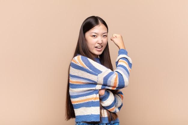 Aziatische jonge vrouw voelt zich gelukkig, tevreden en krachtig, buigt fit en gespierde biceps, ziet er sterk uit voor de sportschool
