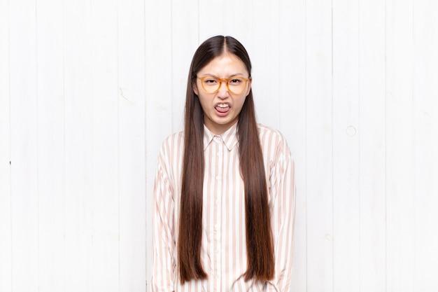 Aziatische jonge vrouw walgt en geïrriteerd, steekt tong uit, houdt niet van iets smerigs en vies
