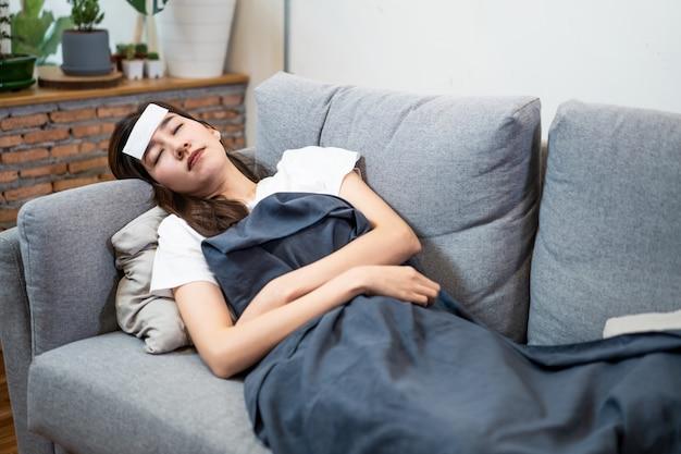 Aziatische jonge vrouw ziek met coronavirus of covid-19 die op hoge temperatuur thuis liggend op bank hebben.