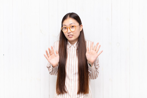 Aziatische jonge vrouw ziet er nerveus, angstig en bezorgd uit, zegt niet mijn schuld of ik heb het niet gedaan