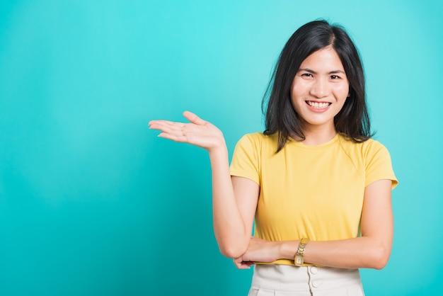 Aziatische jonge vrouw zij die hand toont om product voor te stellen