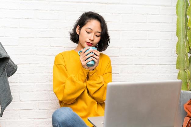 Aziatische jonge vrouw zittend op de vloer met een kopje koffie