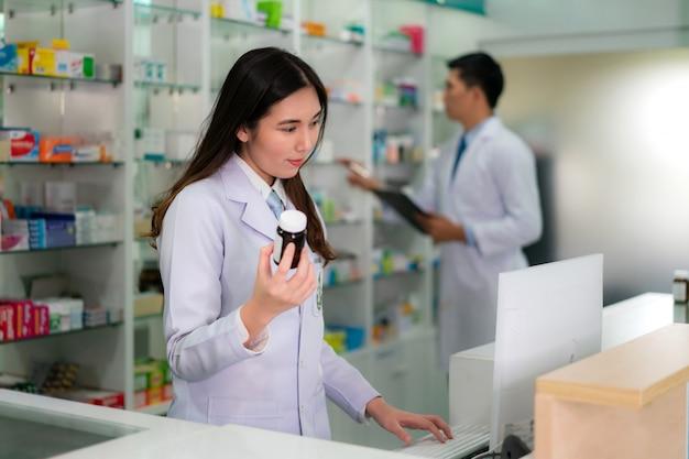 Aziatische jonge vrouwelijke apotheker met glimlach die een geneeskundefles houdt en dat product zoekt in de computer