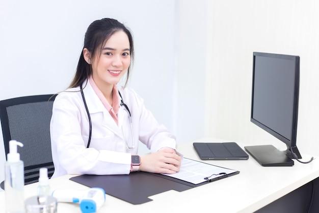 Aziatische jonge vrouwelijke arts in een witte laboratoriumjas zit op kantoorruimte in het ziekenhuis
