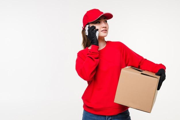 Aziatische jonge vrouwelijke bezorger die zich in witte muur bevindt die mobiele smartphone met behulp van die met klant spreekt die verzendadres controleert