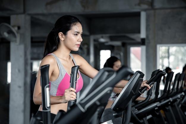 Aziatische jonge vrouwen oefenen met een glimlach uit met de cardio op de oefenmachine in de sportschool. concept van gezondheidszorg met oefening in de sportschool. mooi meisje fitness spelen in de sportschool.