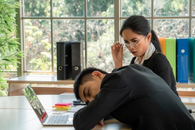 Aziatische jonge vrouwen voelen zich vervelen als ze haar collega's ziet slapen, bedrijfsconcept