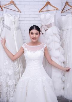 Aziatische jonge vrouwenbruid die op huwelijkskleding proberen bij modern huwelijk