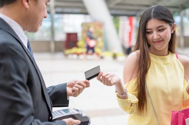 Aziatische jonge vrouwenglimlach met het betalen van creditcard met betaalterminal met verkoper