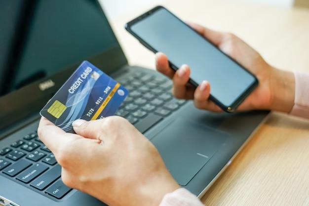 Aziatische jonge vrouwenhanden die creditcard houden en laptop smartphone met behulp van