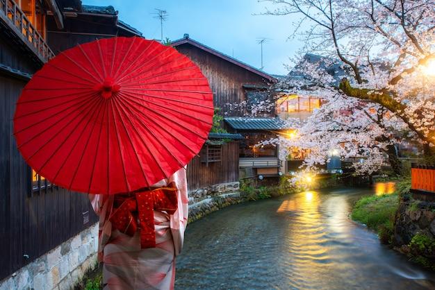 Aziatische jonge vrouwenreiziger die japanse traditionele kimono met rode paraplu dragen die bij de beroemde bloesem van de bestemmingskers bij shirakawa-rivier in het gion-district bij nacht in kyoto, japan bezienswaardigheden bezoeken.