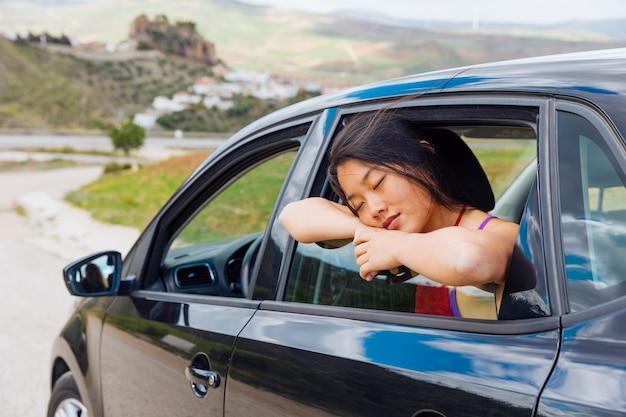 Aziatische jonge vrouwenslaap terwijl het leunen op venster van auto
