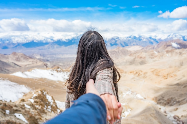 Aziatische jonge vrouwentoerist die laag belangrijke man dragen in mening van de berg van himalayagebergte tegen blauwe hemel
