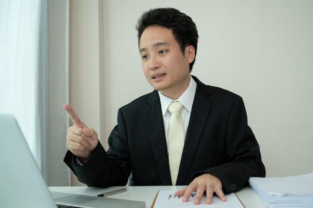 Aziatische jonge zakenman die een online videoconferentie maakt terwijl hij thuis werkt vanwege het coronavirus of de covid-19-pandemie. aziatische zakenman die laptop gebruikt voor online vergadering.