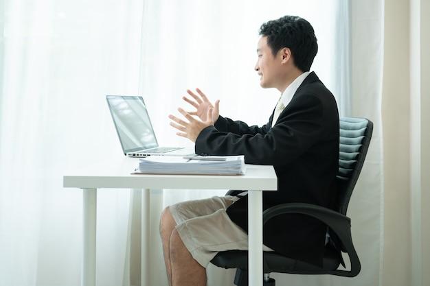 Aziatische jonge zakenman die een online videoconferentie maakt terwijl hij thuis werkt vanwege het coronavirus of de covid-19-pandemie. grappige aziatische zakenman die een formeel pak draagt in bovenlichaam en korte broek