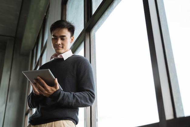 Aziatische jonge zakenman die tabletpc met behulp van