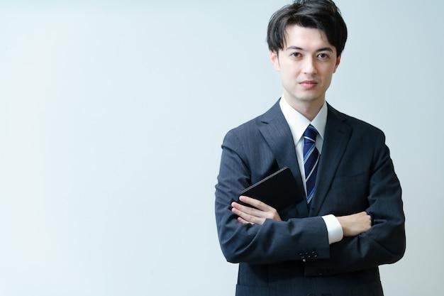 Aziatische jonge zakenman poseren met zijn armen gekruist