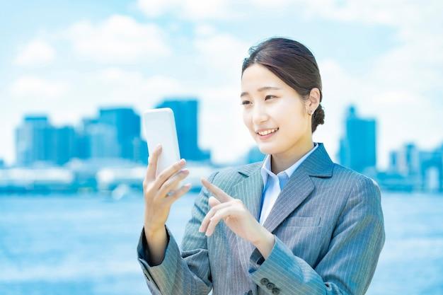 Aziatische jonge zakenvrouw die een smartphone bedient