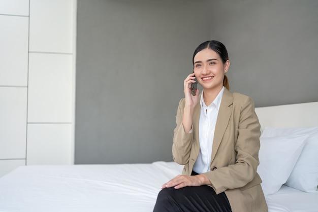 Aziatische jonge zakenvrouw die smartphone in hotelslaapkamer gebruikt op zakenreis