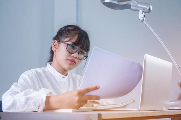 Aziatische jonge zakenvrouw lezing document