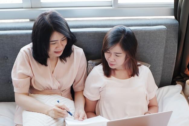 Aziatische jonge zussen die op bed liggen en online op laptop werken