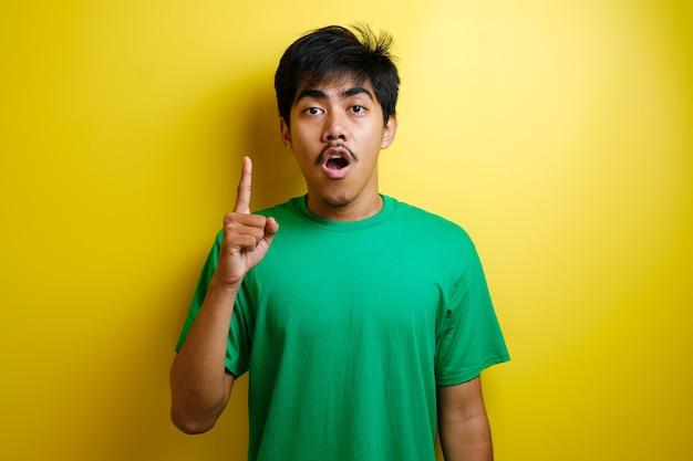 Aziatische jongeman in groen t-shirt zag er gelukkig uit en keek omhoog, met een goed idee. half lichaamsportret tegen gele achtergrond met kopieerruimte