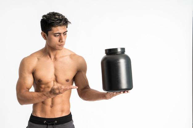 Aziatische jongeman met gespierd lichaam draagt een zwarte fles met één hand terwijl hij aanwezig is en naar voren kijkt en naar de zijkant kijkt