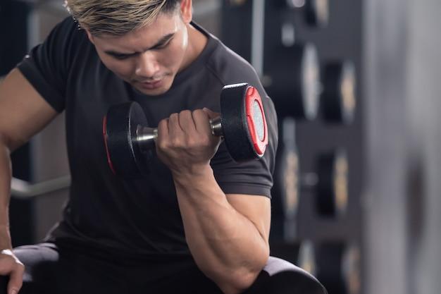 Aziatische jongeman oefent krachttraining in de sportschool, lichaamsbouwoefening. spieropbouw uitdaging concept. sterke sportman tilt een halter op van dichtbij met copyspace.