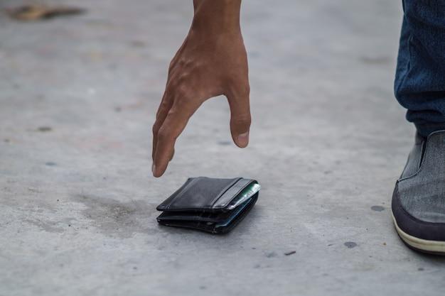 Aziatische jongeman vindt een zwarte portemonnee