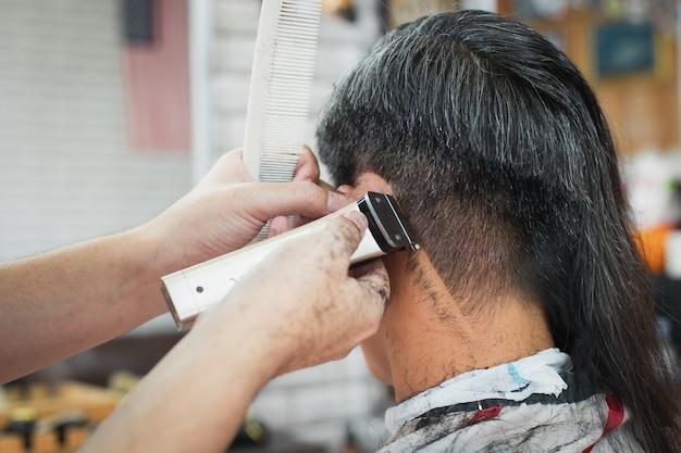 Aziatische jongeman wordt gesneden uit lang haar tot kort haar met een elektrische tondeuse door professionele kapper in de kapsalon.